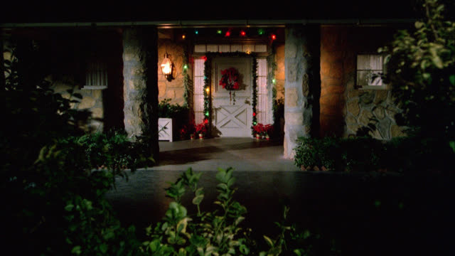 vídeos y material grabado en eventos de stock de zoom in to front door of upper class ranch house with christmas decorations. garland, wreath hangs on front door. christmas lights flash, twinkle rapidly. poinsettias on porch. plants. festive. - efecto zoom