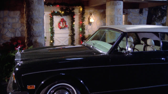 medium angle of ranch style house with christmas decorations, garland, and lights on front entrance door. rolls royce parked in front of house. luxury cars. upper class. - rolls royce videos stock videos & royalty-free footage