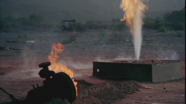 stockvideo's en b-roll-footage met medium angle of crane with hook pulling pipe head away from oil well fire. flames and steam. could be desert. mountains in bg. - olie industrie