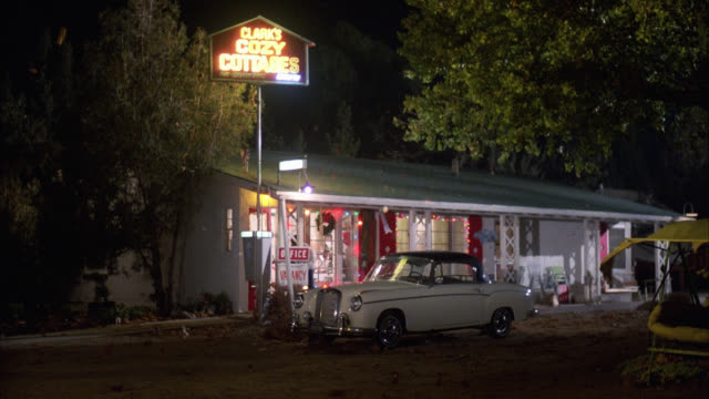 """wide angle of rural motel. neon sign reads """" clark's  cozy cottage."""" colored christmas lights in window. lower class motel. heavy winds blow trees. rolls royce parked out front. woman exits hotel office and camera pans to man sitting in car in shadows. - rolls royce videos stock videos & royalty-free footage"""