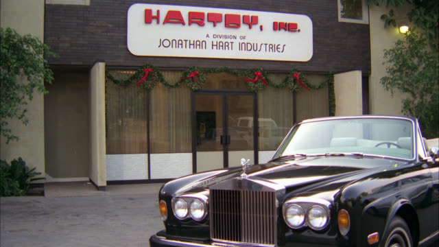 """wide angle of rolls royce convertible car parked in front of building with sign displaying, """"hartoys inc. a division of jonathan hart industries."""" christmas decorations on outside of office building. - rolls royce videos stock videos & royalty-free footage"""
