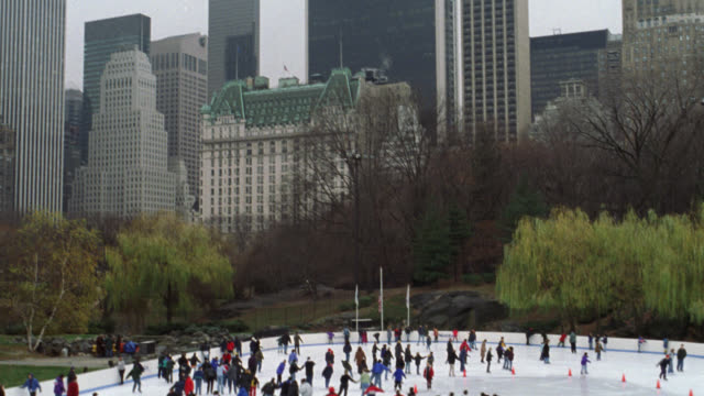 pan down from new york city skyline to wollman ice skating rink in central park. see plaza hotel and office buildings. could be late fall or winter. see many people or families skating. camera pan up to skyline and pan down to rink. downtowns. - ice skating stock videos & royalty-free footage