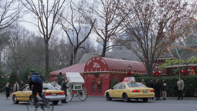 pan right to left of tavern on the green in central park with white christmas lights and decorations. see nyc taxis and a white horse drawn carriage in front of restaurant as people enter and exit. see bicycles pass in foreground and taxis leave. see new - tavern on the green stock videos & royalty-free footage