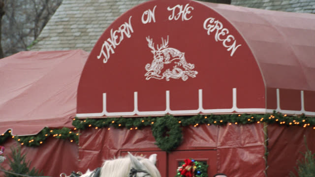 pan left to right from driver and couple in white horse drawn carriage. see parked carriage accelerate. see tavern on the green sign with christmas decorations, lights, and wreaths. pan left across moving carriage to restaurant sign. central park. new yor - tavern on the green stock videos & royalty-free footage