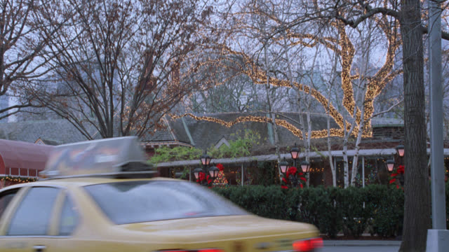 pan right to left of tavern on the green in central park. see christmas lights, decorations, and wreaths. see new york city taxi drive up to entrance. pan left as white horse drawn carriage pulls up to and stops at restaurant entrance. see people leave. c - tavern on the green stock videos & royalty-free footage