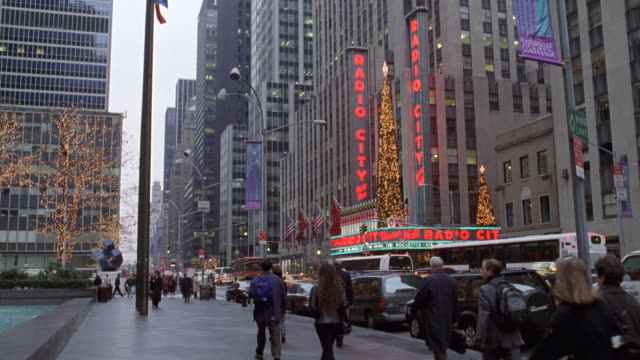 wide angle of 6th avenue or avenue of the americas in new york city. see radio city music hall with christmas decorations and lights. see one-way traffic on street and pedestrians on sidewalk. could be late fall or winter. nyc streets. midtown manhattan. - 1998 stock videos & royalty-free footage
