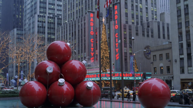 pan right to left of radio city music hall in new york city with fountain in foreground. see large christmas ornaments or decorations sculpture on fountain. see radio city with christmas decorations and lights. see one-way car, taxi, and city bus traffic - radio city music hall stock videos & royalty-free footage