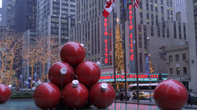 pan left to right of radio city music hall in new york city with fountain in foreground. see large christmas ornaments or decorations sculpture on fountain. see radio city with christmas decorations and lights. see one-way car, taxi, and city bus traffic - radio city music hall stock videos & royalty-free footage