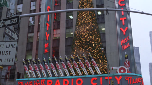 pan down from lit christmas tree on radio city music hall exterior in new york city. see marquee, toy soldiers and cannon christmas decorations, and lights with pedestrians walking in front. see cars, city buses, and taxis driving past. nyc streets. stree - radio city music hall stock videos & royalty-free footage