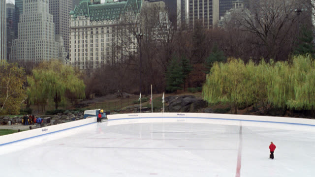 wide angle of ny city skyline with buildings and pan down to empty ice skating rink in central park.  one man on zamboni smoothing out the ice and putting orange cones around dangerous area on ice. wollman rink. overcast. plaza hotel.winter. christmas. mi - ice skating stock videos & royalty-free footage