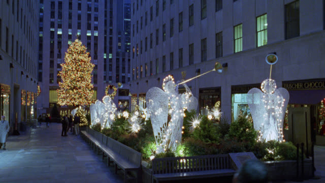 pan left to right of christmas decorations and lights in front of rockefeller center in new york city. see angels with trumpets near storefronts in plaza. see large christmas tree in background near multi-story buildings. could be winter. midtown manhatta - 1998 stock videos & royalty-free footage