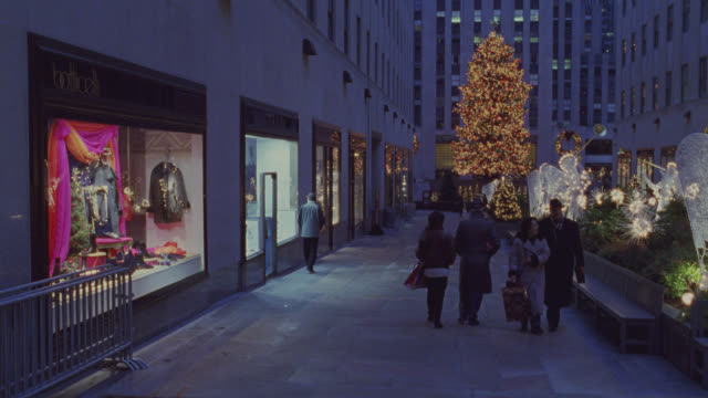 pan left to right of christmas decorations and lights in rockefeller center in new york city. see angels with trumpets near storefronts in plaza as holiday shoppers with gifts pass. see large christmas tree in background near multi-story buildings. could - war in afghanistan: 2001 present stock-videos und b-roll-filmmaterial