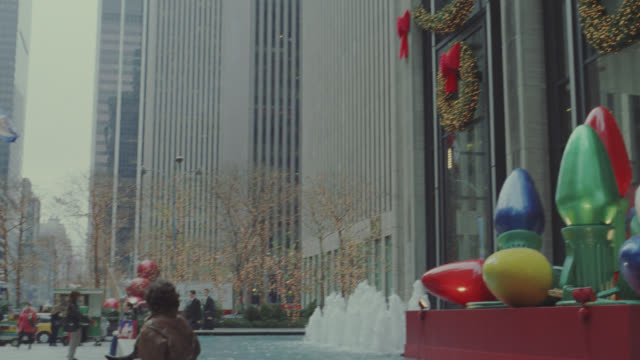 medium angle of street in front of radio city music hall in new york city. see building decorated for christmas with lights. see various multi-story buildings or high rise buildings in background. pan right to see large, toy christmas lights or bulbs.  se - radio city music hall stock videos & royalty-free footage