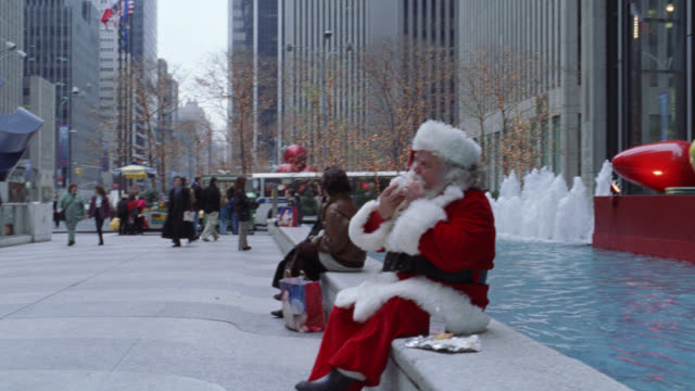 medium angle of man in santa claus costume sitting and eating a slice of pizza on bench in street in front of radio city music hall in new york city. see building decorated for christmas with lights.  multi-story buildings or high rise buildings in backgr - リース点の映像素材/bロール