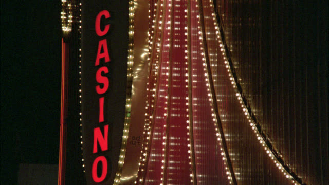 "medium angle of rotating neon sign with flashing lights that reads ""casino"" on one side and ""slow"" on other side. las vegas. - 1987 stock videos & royalty-free footage"