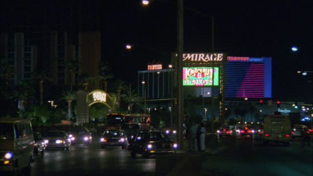 "wide angle of cars driving in both directions down las vegas blvd. mirage hotel and casino with sign reading ""the mirage"" in bg. palm trees. cities. las vegas strip. pedestrians. - the mirage las vegas stock videos & royalty-free footage"