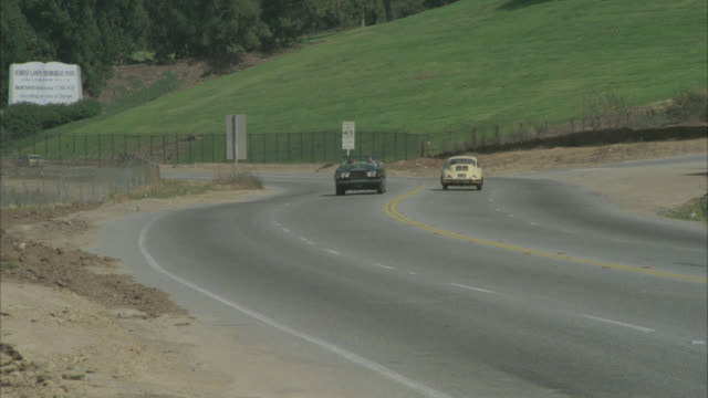 rolls royce convertible with top down driveby l-r with two people / principals / on forest lawn drive - rolls royce stock videos & royalty-free footage