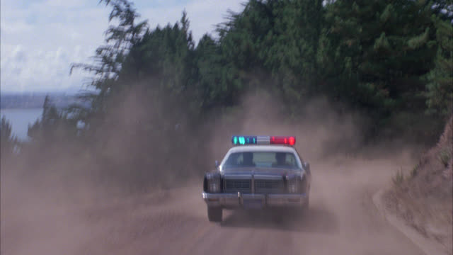 process plate straight back of vehicle speeding on dirt road on side of a mountain while being chased by a police car with bizbar, flashing lights. pine trees, lake in bg. could be big bear. forests. - パトカー点の映像素材/bロール