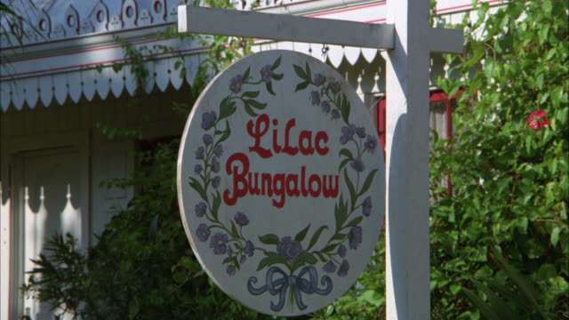vídeos y material grabado en eventos de stock de pull back from sign for lilac bungalow decorated with painted flowers to show two story cottage, guest house, or bungalow. could be victorian. shingled roof. garden. see 6420 thru 6427 - alojamiento y desayuno