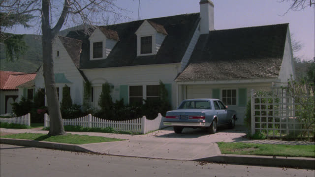 zoom in on two story middle to upper class suburban house with dormer windows. blue car in driveway. white picket fence. neighborhood or residential area. - dormer stock videos and b-roll footage