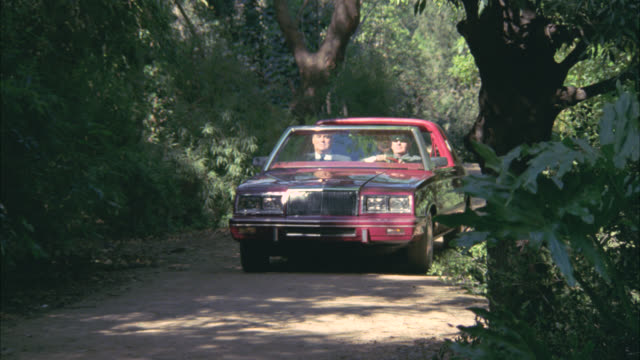 medium angle of convertible lincoln town car driving down dirt road in jungle or forest. two men in car plus driver. men exit car. - lincoln town car stock videos and b-roll footage