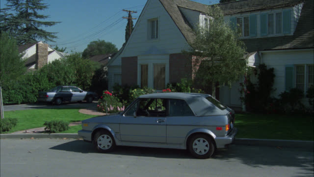 vídeos de stock e filmes b-roll de wide angle of silver volkswagen vw rabbit convertible parked in front of two story house. red brick with white wood. middle class. car parked in driveway. suburban residential area or neighborhood. - sul da califórnia