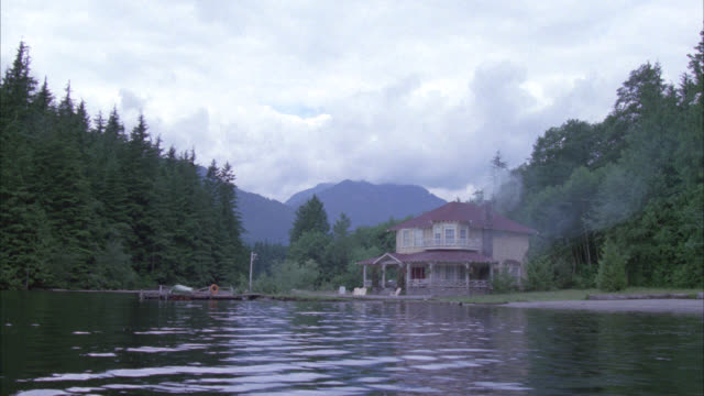 zoom in across lake to two story shingle style house with porch. could be lake house. dock with boat in bg. trees and mountains surround house fog hangs over mountains. chairs on beach or shore. smoke coming out of chimney. - heranzoomen stock-videos und b-roll-filmmaterial