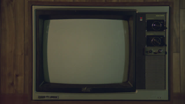 close angle of television set with matte screen and two dials or knobs on right side of screen. wood paneled walls behind television. - matte stock videos & royalty-free footage