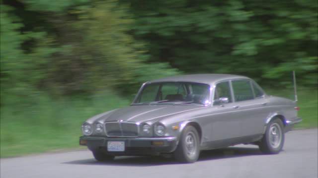 pan right to left of gray or silver jaguar car driving on winding mountain road. dirt road. woods or forest on either side of road. series. - 1996 stock videos & royalty-free footage