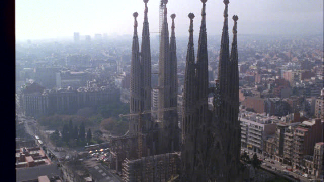 "aerial circling over barcelona's cathedral ""sagrada familia"" or holy family cathedral by antonio gaudi. church has several tall spires or steeples. building is under construction with several cranes in the center of the structure. buildings, city in backg - smog video stock e b–roll"