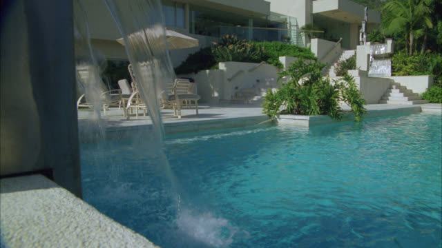 vidéos et rushes de medium angle of a swimming pool with fountain in backyard. could be upper class house or mansion, condominium, apartment building, or hotel.  palm trees. - stéréotype de la classe supérieure