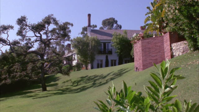 wide angle of two story upper class house or  mansion. lawn and trees in fg. brick wall partially blocking view of house. estates. - zweistöckiges wohnhaus stock-videos und b-roll-filmmaterial