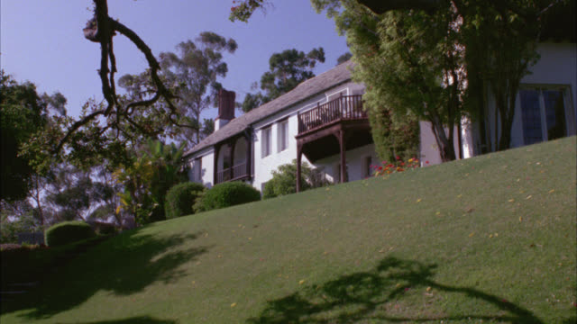 wide angle of two story upper class house or mansion. lawn or yard with trees in fg. estates. - zweistöckiges wohnhaus stock-videos und b-roll-filmmaterial