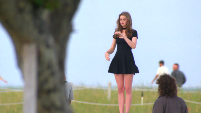 hand held of young woman in a short black dress standing on a concrete wall at the boardwalk in miami. people standing, sitting near woman. beachgrass on sandy hill and ocean in bg. - black dress stock videos & royalty-free footage