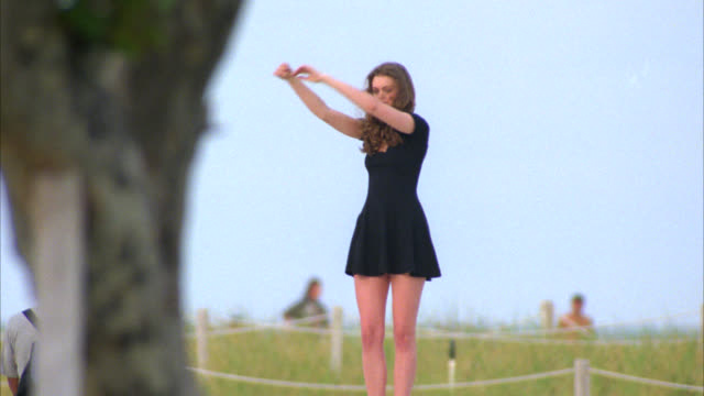 hand held of photographer taking pictures of young brunette woman posing in a short black dress standing on a concrete wall at the boardwalk in miami. whip pan around to other people standing and sitting. photo shoot. beachgrass on sandy hill and ocean in - black dress stock videos & royalty-free footage