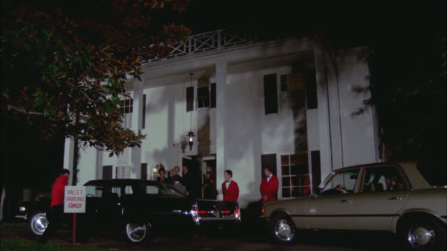 "wide angle of two story, upper class, greek revival house or mansion with guests driving to entrance of house. people assisted by valets in red jackets. sign reading ""valet parking only"". cadallac, mercedes-benz pull up to valet parking. could be used for - stereotypically upper class stock videos & royalty-free footage"