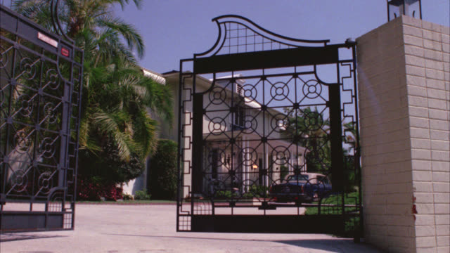 wide angle of two story upper class house or mansion with open gate in fg. rolls royce car parked in driveway.  elaborate iron gates slowly closes creating sense of exclusivity. palm trees on side of house. could be beverly hills or bel air. - gate stock videos & royalty-free footage