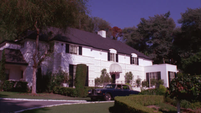 wide angle of  upper class, two-story house or mansion with shutters and a rolls royce convertible parked in driveway. house is surrounded by trees, hedges. white awning over front entrance to house. upper class. los angeles. could be beverly hills or bel - beverly hills bildbanksvideor och videomaterial från bakom kulisserna