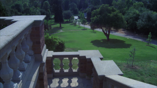 pan right to left from high angle down of mansion stairs or balcony to ford mustang as it approaches mansion or estate. camera pans left to right as car moves up driveway. upper class tudor style mansion  large fountain in courtyard. american flag on flag - herrenhaus stock-videos und b-roll-filmmaterial