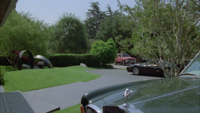 medium angle of sports cars parked in upper class driveway. lamborghini and rolls royce. red gmc jimmy suv or truck pulls into driveway. two men exit and approach front door to house. art or sculpture and trees. - rolls royce videos stock videos & royalty-free footage