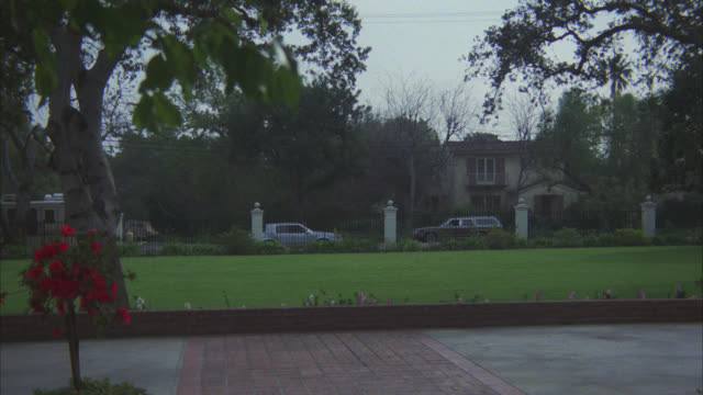 wide angle of front lawn and driveways of mansion or upper class house. large iron fence will in bg. cars parked on curb across street near another large house. trees. red gmc jimmy suv pulls up in driveway. - wide angle stock videos & royalty-free footage