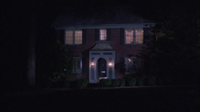 wide angle of two story colonial middle class brick house at night. entry way and second story lights on. cars drive by left to right and right to left. headlights. - zweistöckiges wohnhaus stock-videos und b-roll-filmmaterial