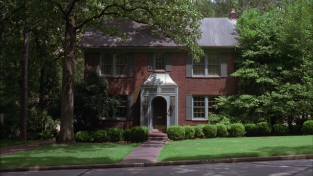 vidéos et rushes de wide angle of red colonial brick two-story house surrounded by trees. could be either middle class or upper class. suburbs. residential areas. - banlieue pavillonnaire