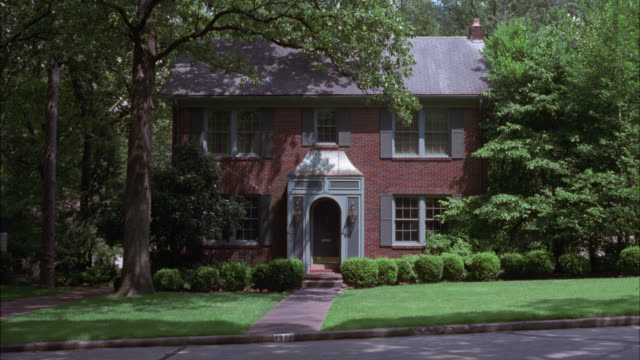 wide angle of red colonial brick two-story house surrounded by trees. could be either middle class or upper class. suburbs. residential areas. car drives by from right to left. - zweistöckiges wohnhaus stock-videos und b-roll-filmmaterial
