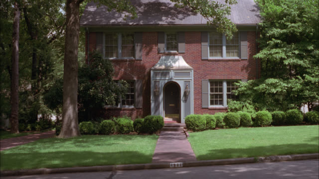 wide angle of red colonial brick two story house surrounded by shade trees. could be either middle class or upper class. suburbs. residential areas. - zweistöckiges wohnhaus stock-videos und b-roll-filmmaterial