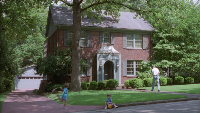 wide angle of red colonial brick two-story house surrounded by trees. garage visible behind house. upper class or middle class. suburbs. residential areas. young boy sits on curb playing with ball while young girl skips or jumps rope in driveway. man swee - stereotypically middle class stock videos & royalty-free footage