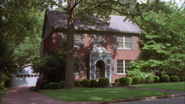 wide angle of red brick, colonial style, two-story house surrounded by trees. garage on left in bg. could be upper class or middle class suburbs. residential areas. - brick house stock videos & royalty-free footage