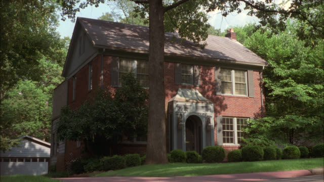 medium angle of red brick, colonial style, two-story house surrounded by trees. garage on left in bg. could be upper class or middle class suburbs. residential areas. group of boys runs past house from right to left. boy on bicycle chases after them. play - brick house stock videos & royalty-free footage