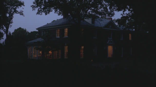 wide angle of two-story, red brick mansion or estate. small closed in glass porch attached to house. trees surround property. multiple takes. lights on at dusk. - zweistöckiges wohnhaus stock-videos und b-roll-filmmaterial