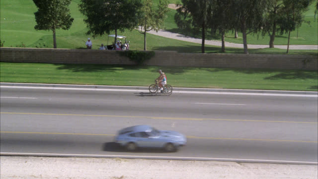 aerial of two bicyclists riding on road adjacent to golf course in palm springs. busy street with cars, traffic. trees, pond. grass, fairways, bunkers. could be resort or country club. - palm springs california pool stock videos & royalty-free footage